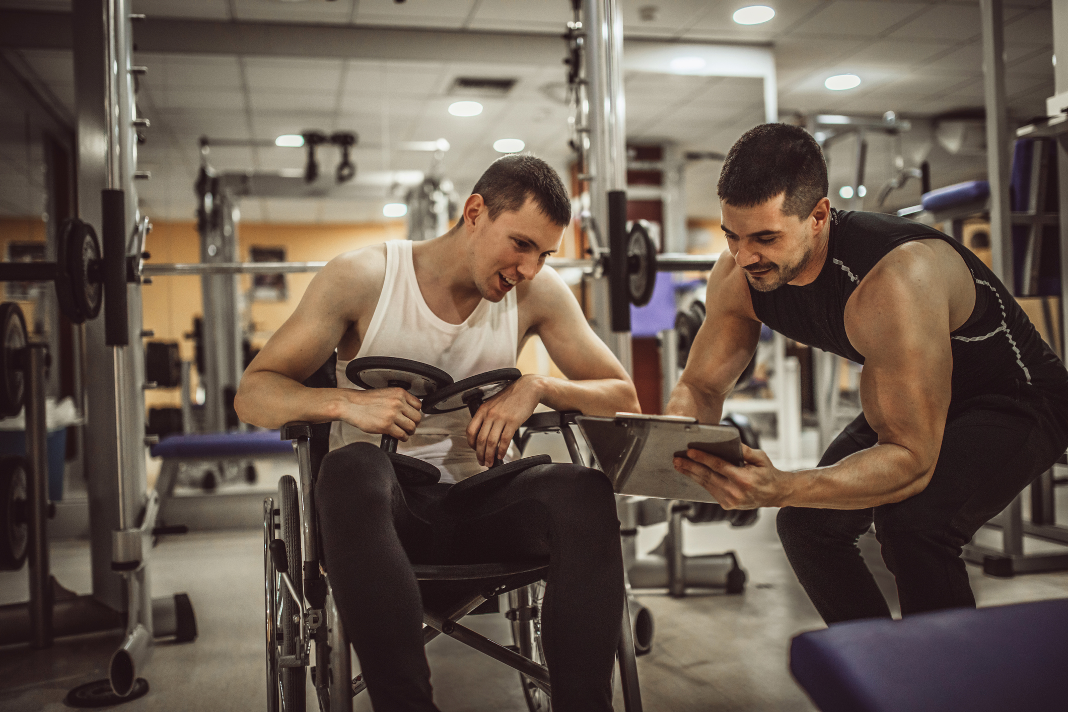 certifystrong-Personal Trainer helping patient in wheelchair in the gym